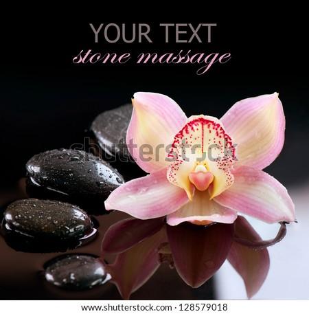 Spa Stones and Orchid Flower. Stone Massage. Black Basalt Stones over Dark Background - stock photo