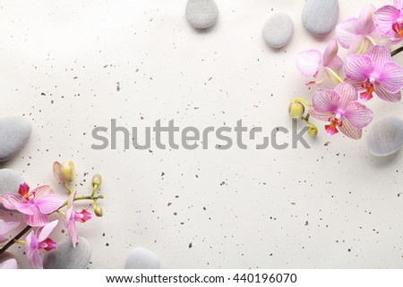 Spa Stones and Orchid flowers on paper - stock photo