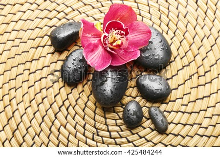 Spa stones and red orchid on a wicker mat, closeup - stock photo