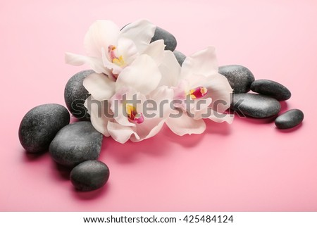 Spa stones and white orchid on pink background