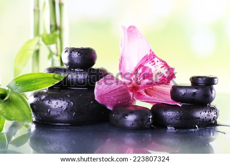 Spa stones, bamboo branches and lilac orchid on table on natural background - stock photo