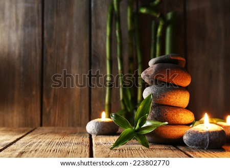 Spa stones, candles, bamboo branches on wooden table on dark background - stock photo
