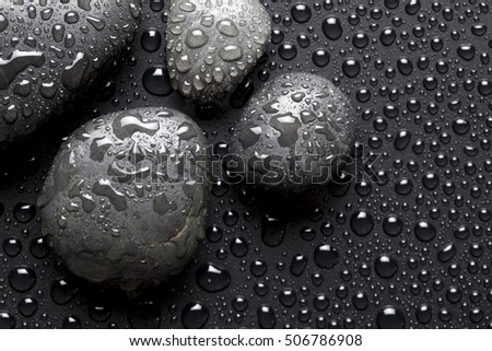 Spa stones on black dewy background