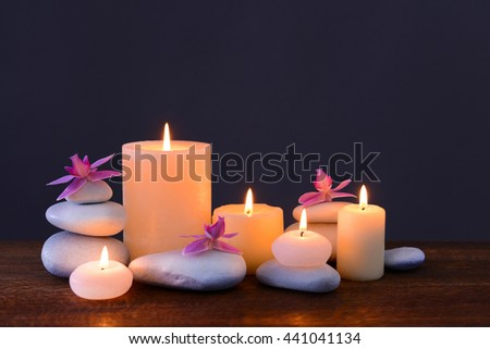 Spa stones with burning candles and flowers on grey background - stock photo