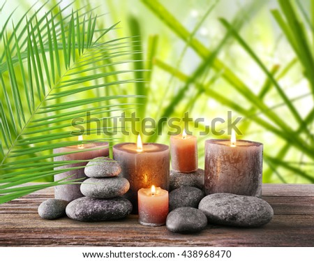 Spa stones with burning candles and flowers on natural background - stock photo
