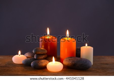 Spa stones with burning candles on grey background - stock photo
