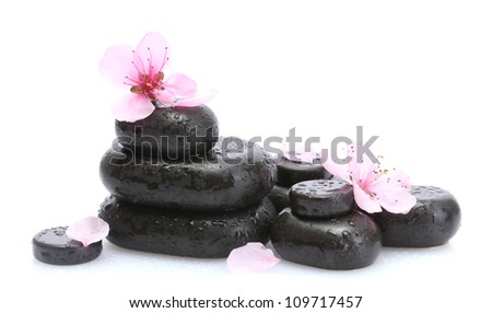 Spa stones with drops and pink sakura flowers isolated on white