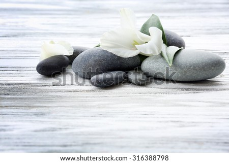 Spa stones with flower and green leaves on wooden background - stock photo