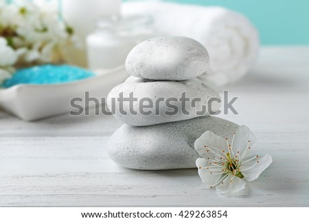 Spa stones with flower on white wooden table