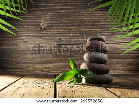 Spa stones with green leaves on wooden background - stock photo