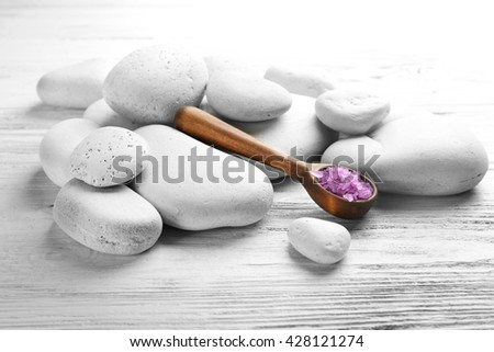 Spa stones with salt on white wooden background