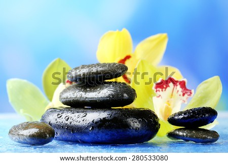 Spa stones with steam and beautiful blooming orchid on blue background - stock photo