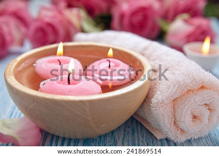 Spa theme with candles and flowers on wooden background - stock photo