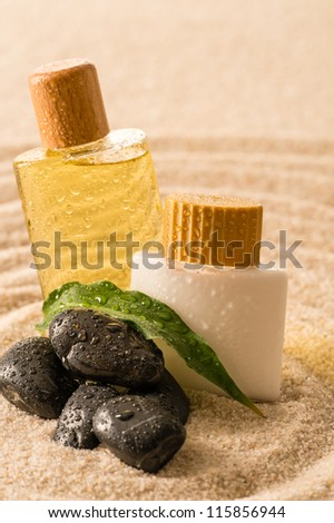 Spa therapy cosmetic products with zen stones on sand - stock photo