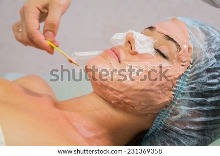Spa therapy for young woman receiving facial mask at beauty salon.Cosmetic truant, spa, beauty, skin, rubber mask - the concept of skin care. Article about cosmetology. - stock photo