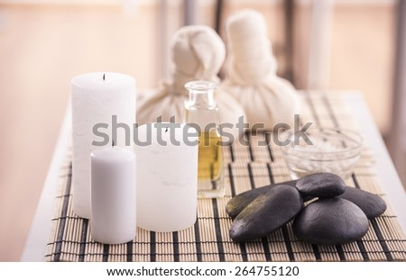 Spa therapy. Spa concept. Zen basalt stones, spa oil, spa herbal balls and sea salt. - stock photo