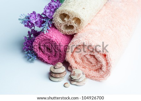 Spa towels rolls, flower and stones lying on shite background. Horizontal composition. - stock photo