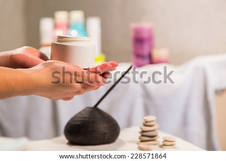 Spa treatment for hands. Application of hand cream in a spa salon. Manicure, hand care. Relaxation, fun, hands, care background. Candles in the background. - stock photo