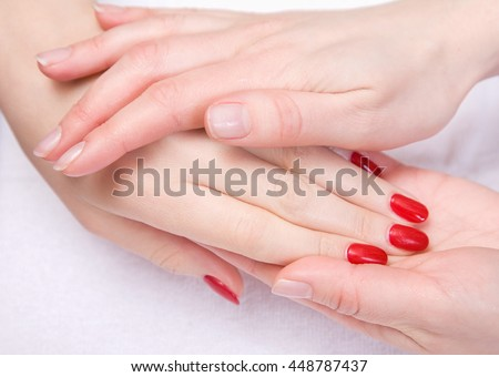 SPA treatment, hand massage and body care. beautiful female hand with red manicure close up.