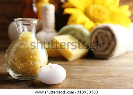 Spa treatments and sunflower on wooden background