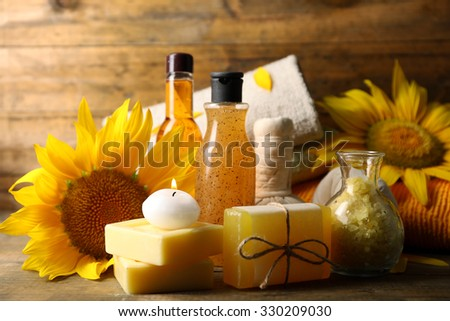 Spa treatments and sunflower on wooden background - stock photo