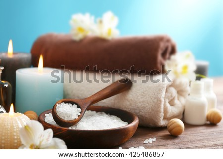 Spa treatments on wooden table against blue background