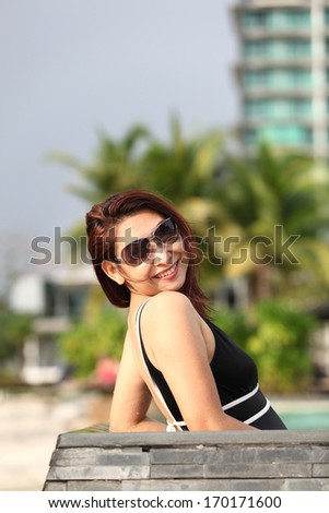 Spa vacation retreat woman relaxing at luxury travel resort. Happy blissful asian young woman in bikini in meditation enjoying summer sun and tanning during holidays .  - stock photo