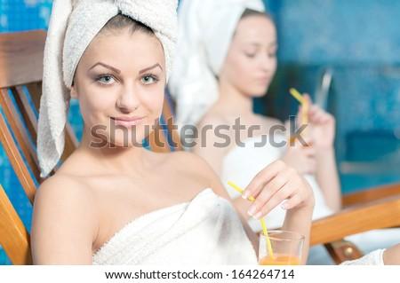 Spa & Wellness. Girls in bathrobe drinking juice in spa salon - stock photo