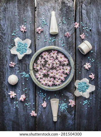 Spa Wellness treatment set and  body care cosmetics,  blue sea salt , bowl with flowers in water on rustic wooden background, top view - stock photo