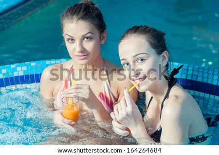 Spa & Wellness. young women relaxing in outdoor jacuzzi by the pool