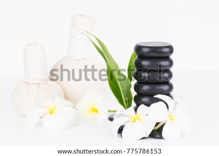 Spa with hot stones, herbal compress balls and flowers on white background