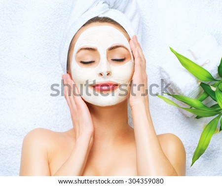 Spa Woman applying Facial cleansing Mask. Beauty Treatments. Clay mask - stock photo