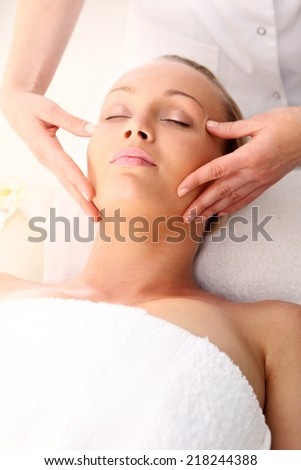 Spa -  woman at face massage .Beautician beautiful woman massaging her temples . Woman in a beauty salon. Masseur massaging a woman in a spa. - stock photo