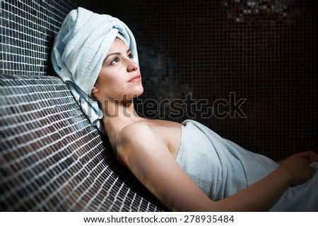 Spa woman.Beautiful girl after bath in jacuzzi spa,relaxing after massage,wrapped in towels.Skincare.Perfect smooth young exfoliated skin.Woman pleased with the results from the spa treatments - stock photo