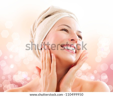 Spa Woman. Beautiful Girl After Bath Touching Her Face. Perfect Skin. Skincare. Young Skin. Girl Pleased with the Results from the Spa Treatments - stock photo