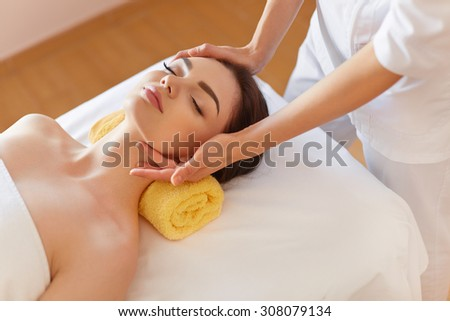 Spa Woman. Beautiful Young Woman Getting a Face Treatment at Beauty Salon. Face Massage - stock photo