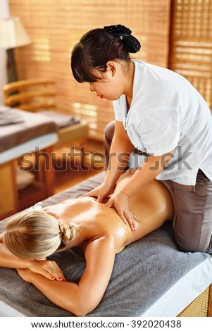 Spa Woman. Beauty Treatment. Close-up Of Sexy Healthy Girl Enjoying Relaxing Hand Massage Procedure In Cosmetology Spa Centre, Salon. Masseur Massaging Female Back With Oil. Body, Skin Care Therapy - stock photo