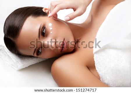 Spa Woman. Close-up of a Young Woman Getting Spa Treatment. Cosmetic Cream on a Cheek. Skin Care