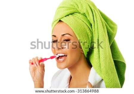 Spa woman in bathrobe brushing teeth. - stock photo