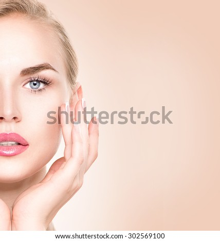 Spa Woman Portrait. Beautiful Girl Touching her Face. Perfect Fresh Skin. Pure Beauty Model Female looking at camera. Youth and Skin Care Concept - stock photo