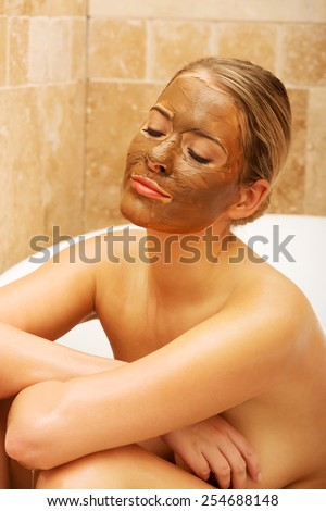 Spa woman sitting in a bath with chocolate mask on face. - stock photo