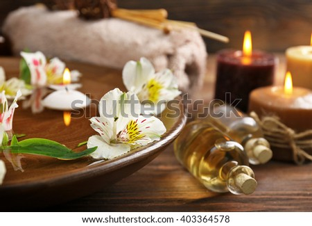 Spa wooden bowl with water and flowers closeup - stock photo