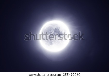 Space background - bright full supermoon in the night sky with glowing edges - stock photo
