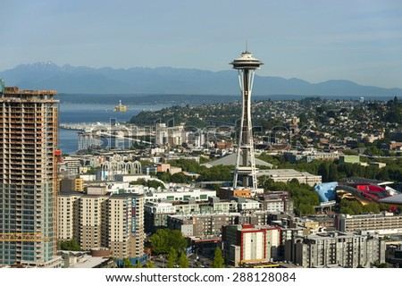 Space Needle and an off shore oil rig. An oil drilling platform is escorted north by tug boats out of Seattle, Washington returning to Alaska.  - stock photo