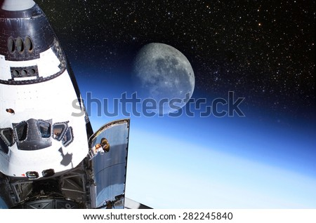 Space Shuttle orbiting the earth with moon background. Elements of this image furnished by NASA. - stock photo