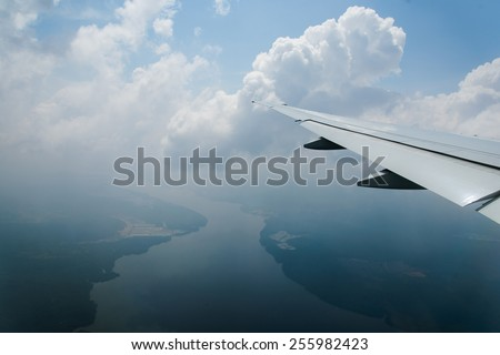 space view from airliner window with blue sky and clouds