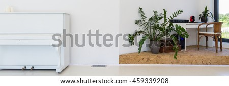 Space with a white piano and corner with a desk, chair and flower pot with a palm