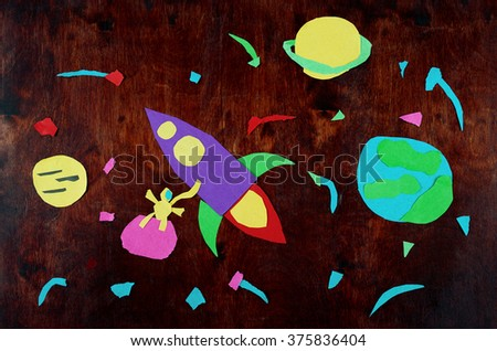 Spaceship in space. Applique made by child from paper on wood. - stock photo