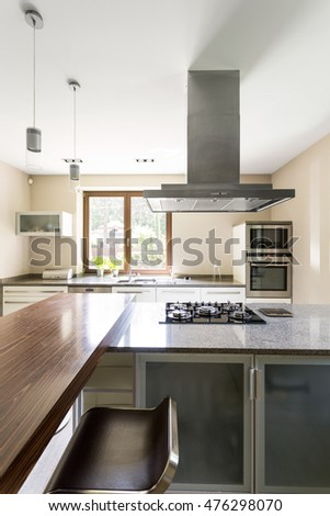 Spacious and minimalist kitchen with marble kitchen top and chrome eave