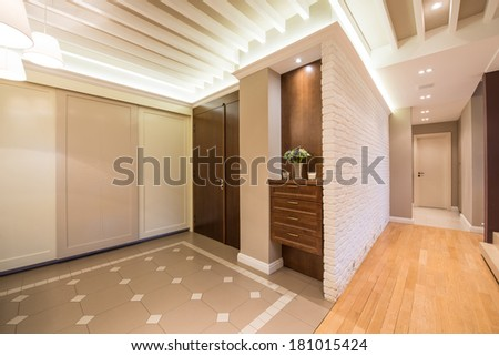 Spacious anteroom interior in warm tones and modern ceiling lights - stock photo